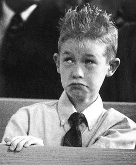 Bored kid with spiked hair at wedding.